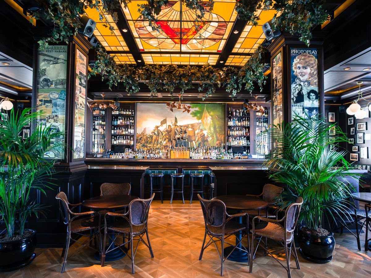 Blacktail's dark bar, surrounded by two plants and a golden stained glass ceiling