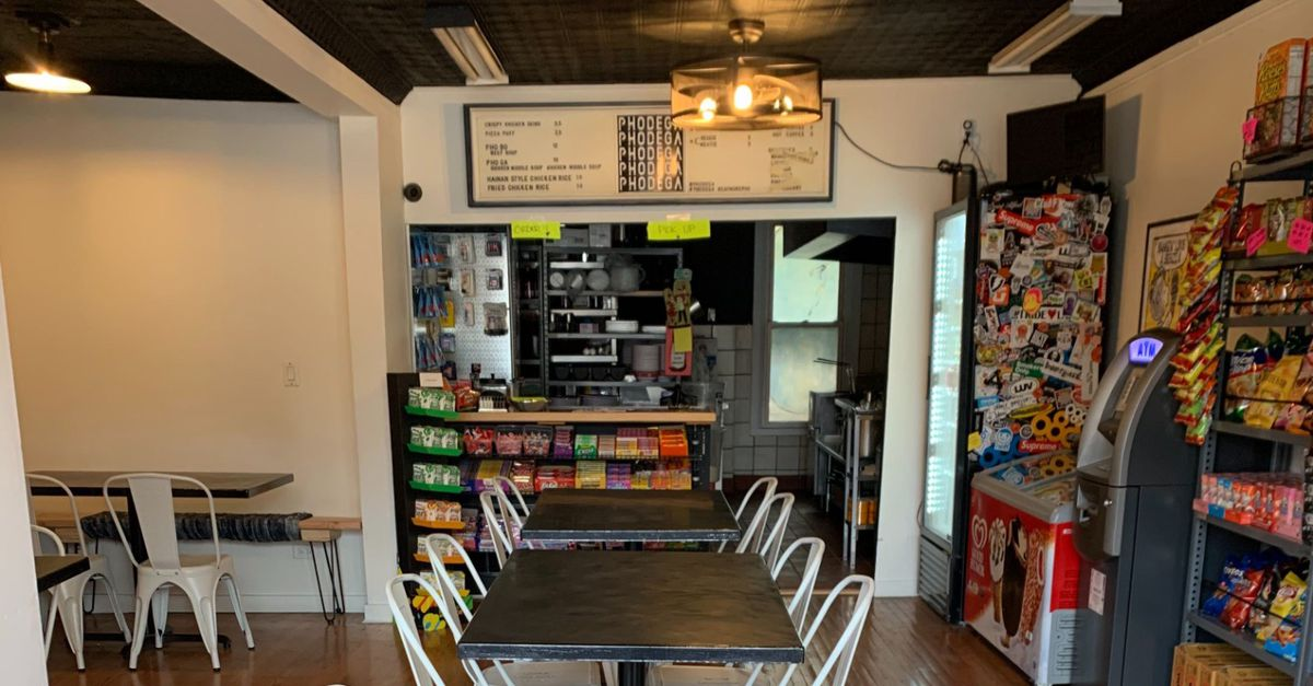 Inside a pho restaurant and convenient store with a menu over a counter, racks of goods, and a black table.