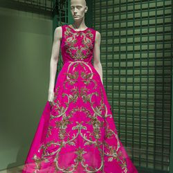 A sleeveless jewel-neck hot-pink gown with metallic embellishment, from fall 2013, in the Garden section of the exhibit.