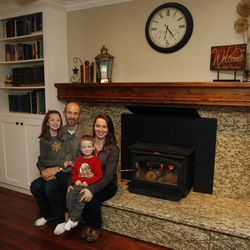 Timothy and Esther Olschewski and two of their six children, Jordan, 9, and Moroni, 3, gather around their Lennox Perform C210 Phase II EPA-certified wood-burning stove in their home in West Valley City Thursday, Jan. 8, 2015. The stove has a two-tier burning system that emits cleaner fumes.