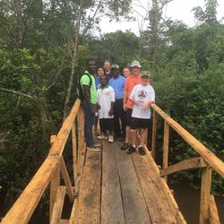 Members of the expedition and some Ghanians stand on a bridge the group built with funds raised for Myan Moon's Eagle project.