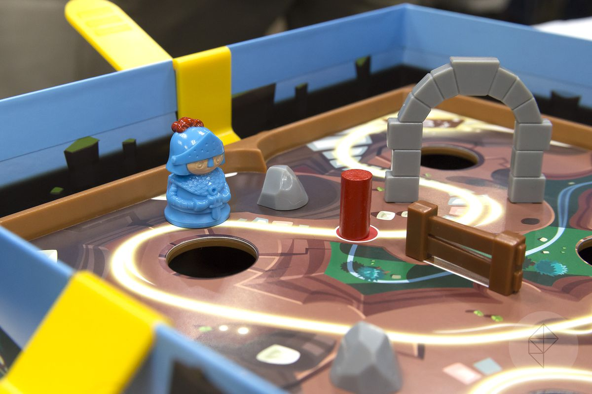 The blue player pawn stands near a hole in the Labyrinth-like game board. There's a plastic rock and a piece of dynamite in between him and the next arch on the path to freedom.