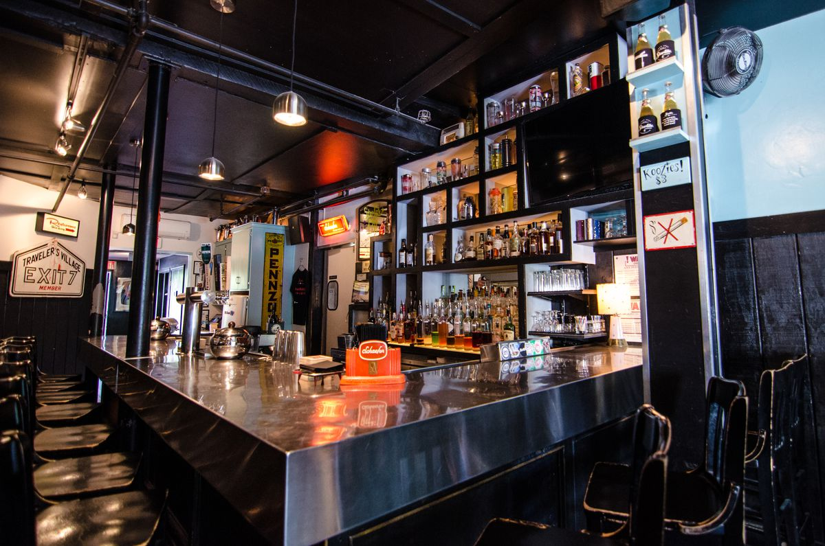 A neighborhood bar with black and turquoise accents and various pieces of vintage signage