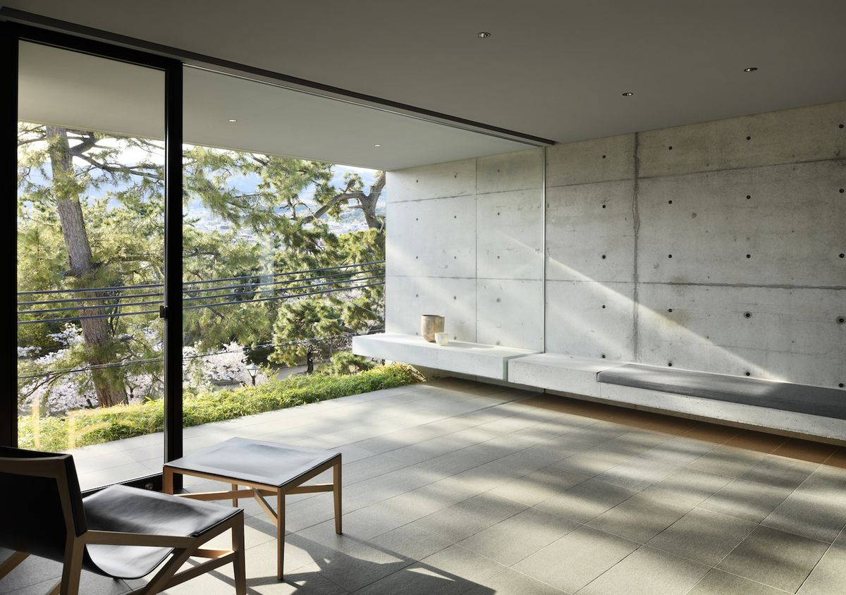 Room with concrete walls and bench, with natural light filtering in,