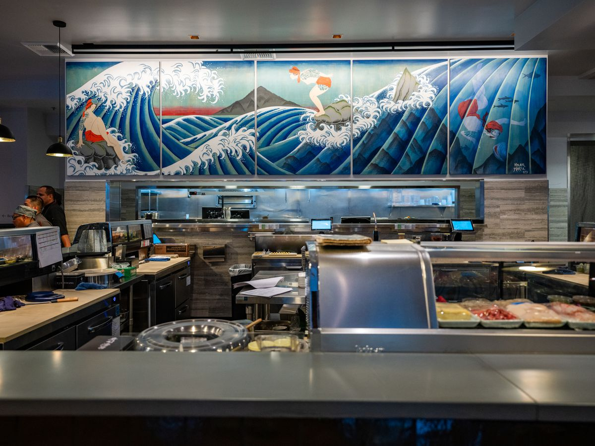 Bamboo Sushi's kitchen with a colorful mural in the back depicting surfers.