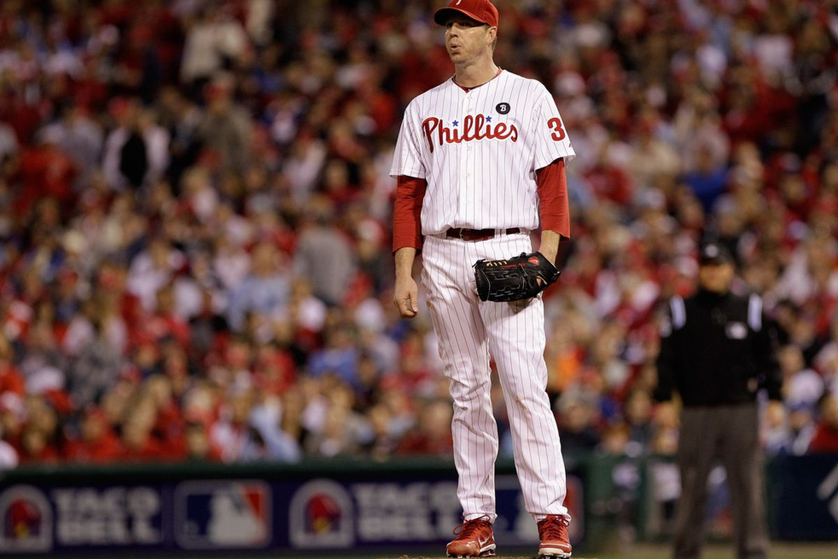 """Pausing amidst a 1-0 game to ponder the meaning of life, Roy Halladay wonders to himself, """"Maybe Nietzsche was right.""""  (Photo by Rob Carr/Getty Images)"""