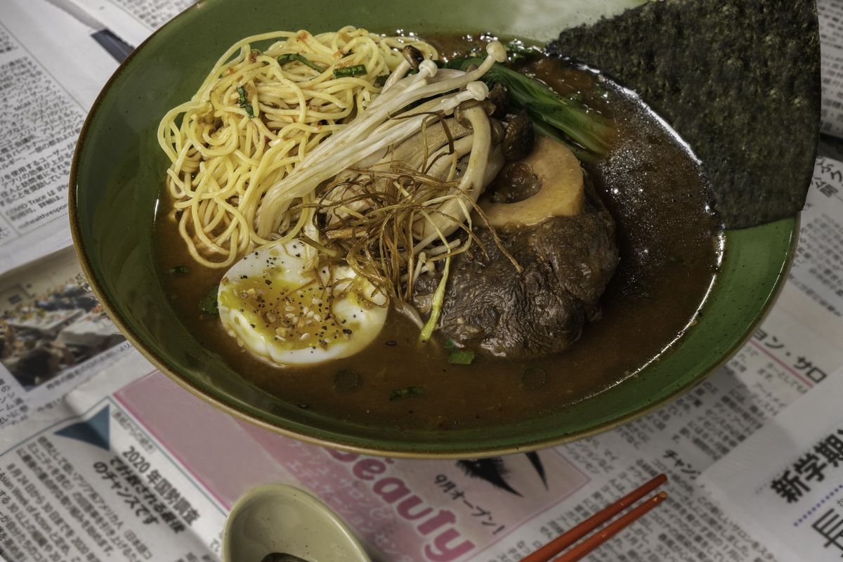 A bowl of ramen with newspaper underneath