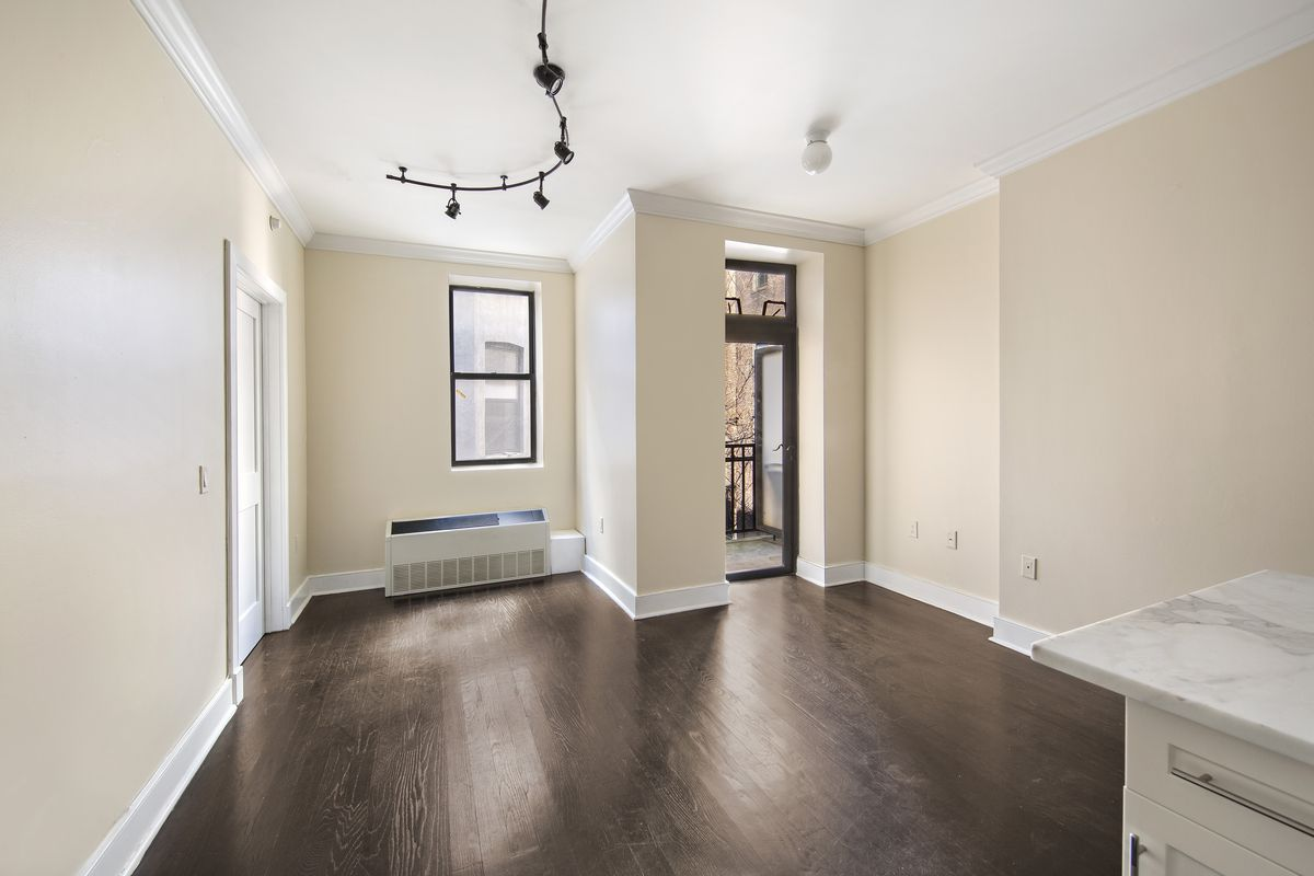 A living area with hardwood floors, beige walls, and crown moldings.