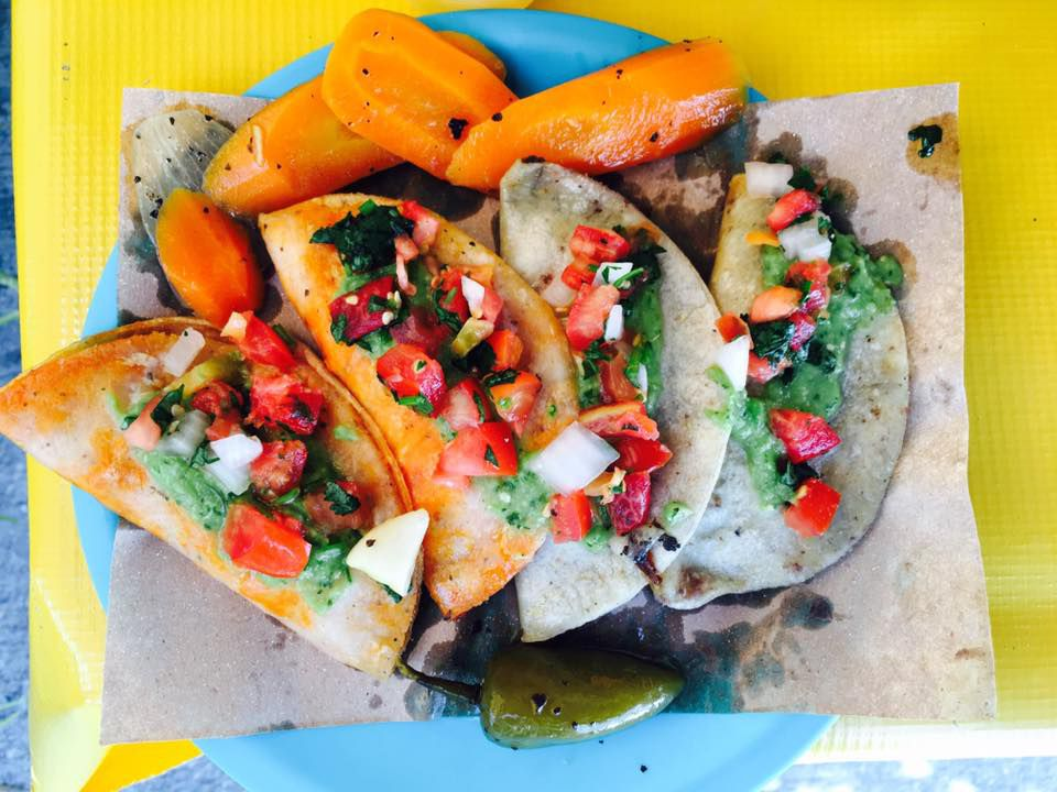 Several tacos laid across a plate, topped with salsa and roasted vegetables, on a bright background
