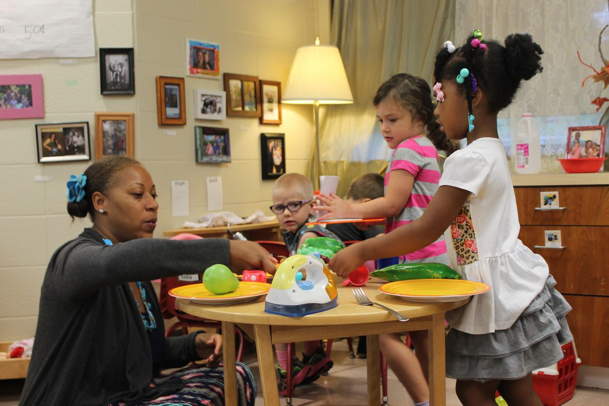 A teacher sits with preschoolers as they play in a preschool classroom at the Day Early Learning Lilly Center.