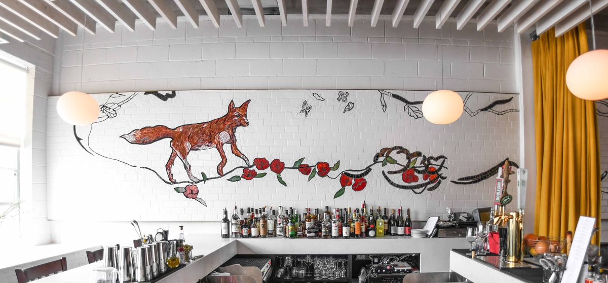 A tile mural depicting a fox and poppies by Laura Rendlen at Novel