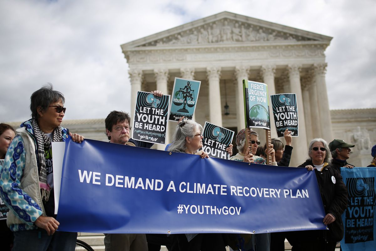 "Protesters attend a rally outside the US Supreme Court held by the group Our Children's Trust on October 29, 2018. Their banner reads, ""We demand a climate recovery plan #youthvgov."""