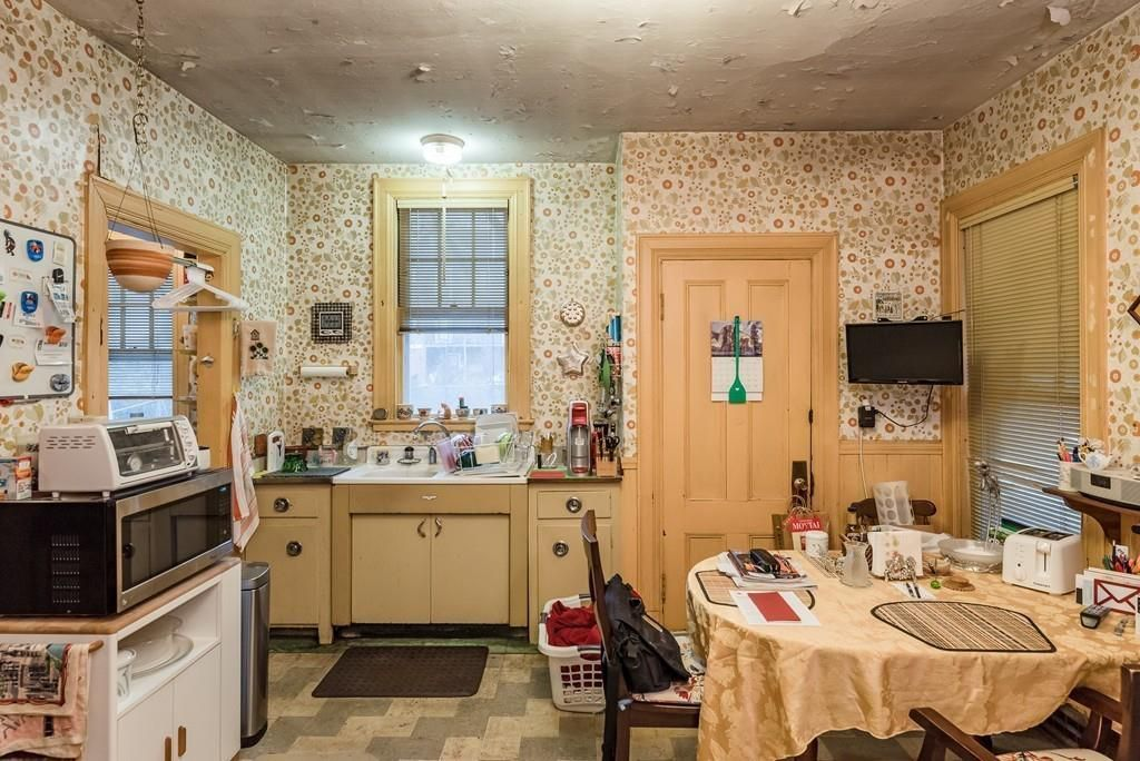 A somewhat cluttered kitchen with a run of counter next to a pantry, and a table and chairs in the foreground.