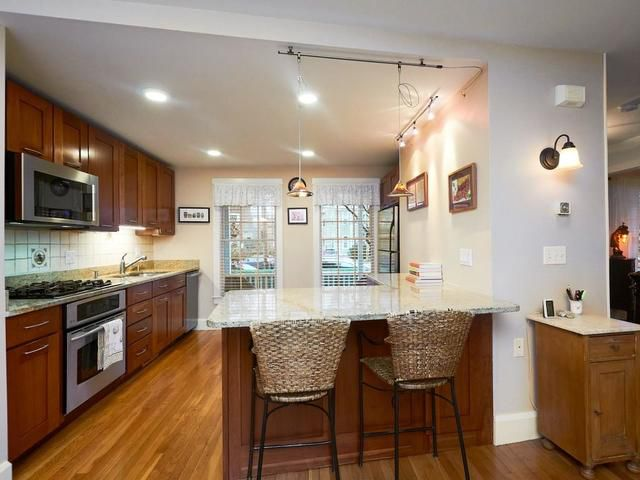 A kitchen with one long counter and then a shorter one jutting out with chairs in front of it.
