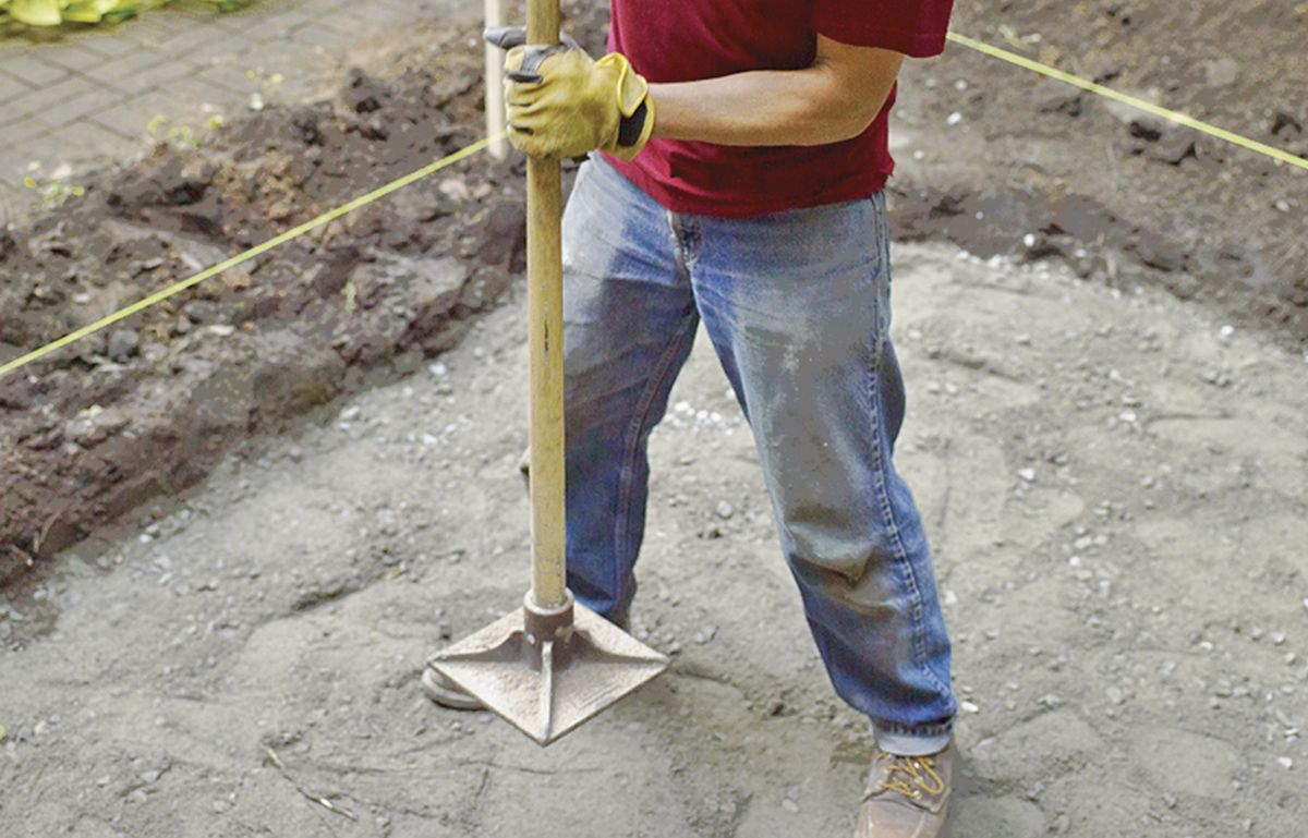 Man Uses Paver Base to Pack Base For Bluestone Patio