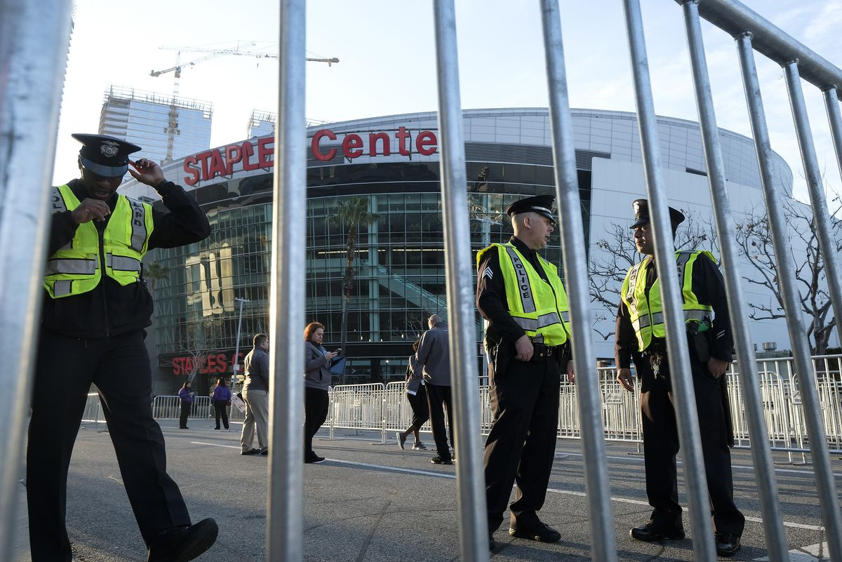 Police officers are shown outside the Staples Center before a public memorial for former Los Angeles Lakers star Kobe Bryant and his daughter, Gianna, in Los Angeles, Monday, Feb. 24, 2020. (AP Photo/Ringo H.W. Chiu)