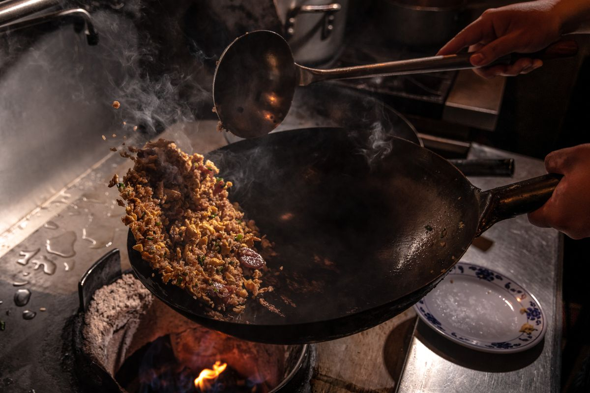 A rice dish being cooked in a wok with a ladle