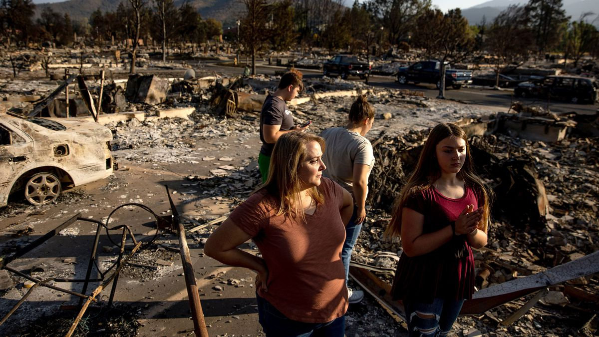 Misty Pantle and her children, Tanner, 15, Tatum, 16, and Reese, 14, left to right, make the first visit to the burned remnants of the home they and Pantle's sister Tammy Johnson, not pictured, shared in Talent, Ore., on Saturday, Sept. 19, 2020. Their home was one of more than 2,300 residences destroyed when the Almeda Fire swept through the towns of Talent and Phoenix in southern Oregon.