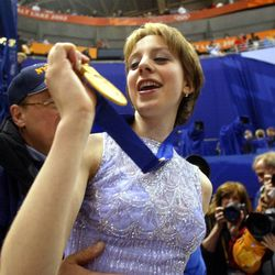 Sarah Hughes of the U.S. looks at her gold medal after kissing her dad, John, while her mom, Amy, looks on after winning the gold medal after her free program on Thursday, Feb 21, 2002, at the Salt Lake Ice Center.