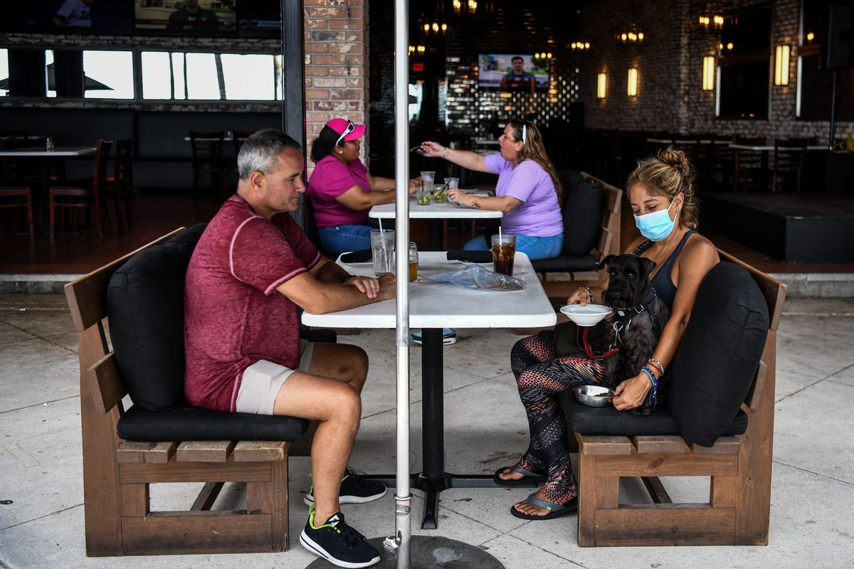 A maskless man looks across a table at a masked woman with a black dog in her lap, which she is giving water to.