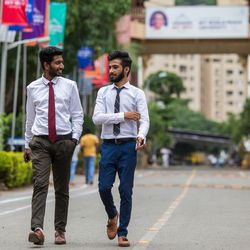 Tarun Marthano, left, and Kishan Demda walk after an interview  at the MIT World Peace university in Pune, Maharashtra, India, on August 15, 2017.