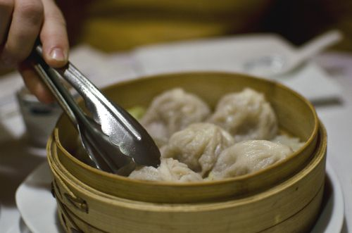 A hand, holding metal tongs, reaches into a steamer basket full of soup dumplings
