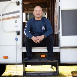 Julio Rosales, 51, photographed inside the doorframe of his RV parked in Stephenville, Texas. Julio is a juggler in a circus, but because the circuses are shut down, he is doing whatever odd jobs at fairs and carnivals that he can pick up. He's currently selling cotton candy at a carnival at a shopping center.