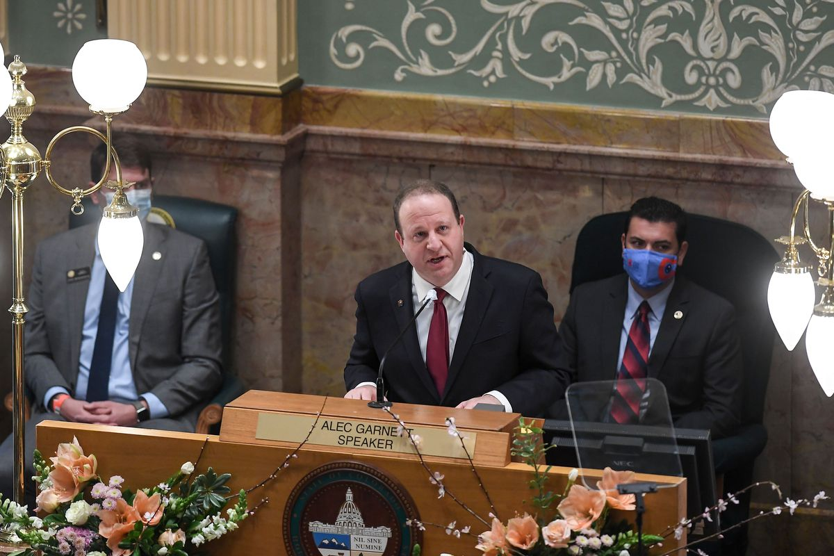 Gov. Jared Polis, flanked by two masked officials, stands at lectern speaking