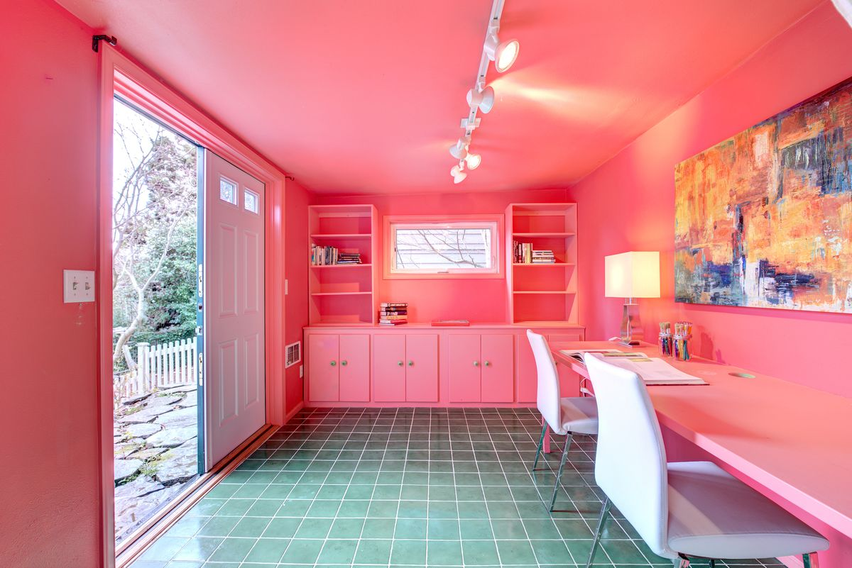 An all-pink office with green floor tile has French doors leading out to a backyard