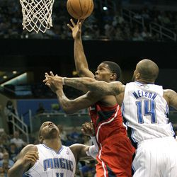 Atlanta Hawks' Joe Johnson makes a move to the basket as he gets between Orlando Magic's Glen Davis (11) and Jameer Nelson (14) during the first half of an NBA basketball game on Friday, April 13, 2012, in Orlando, Fla.