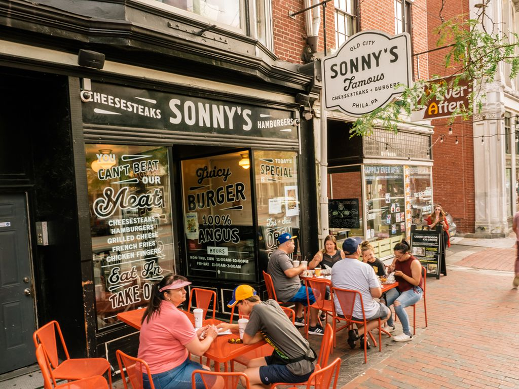 Outside of Sonny's, with orange chairs and people eating cheesesteaks
