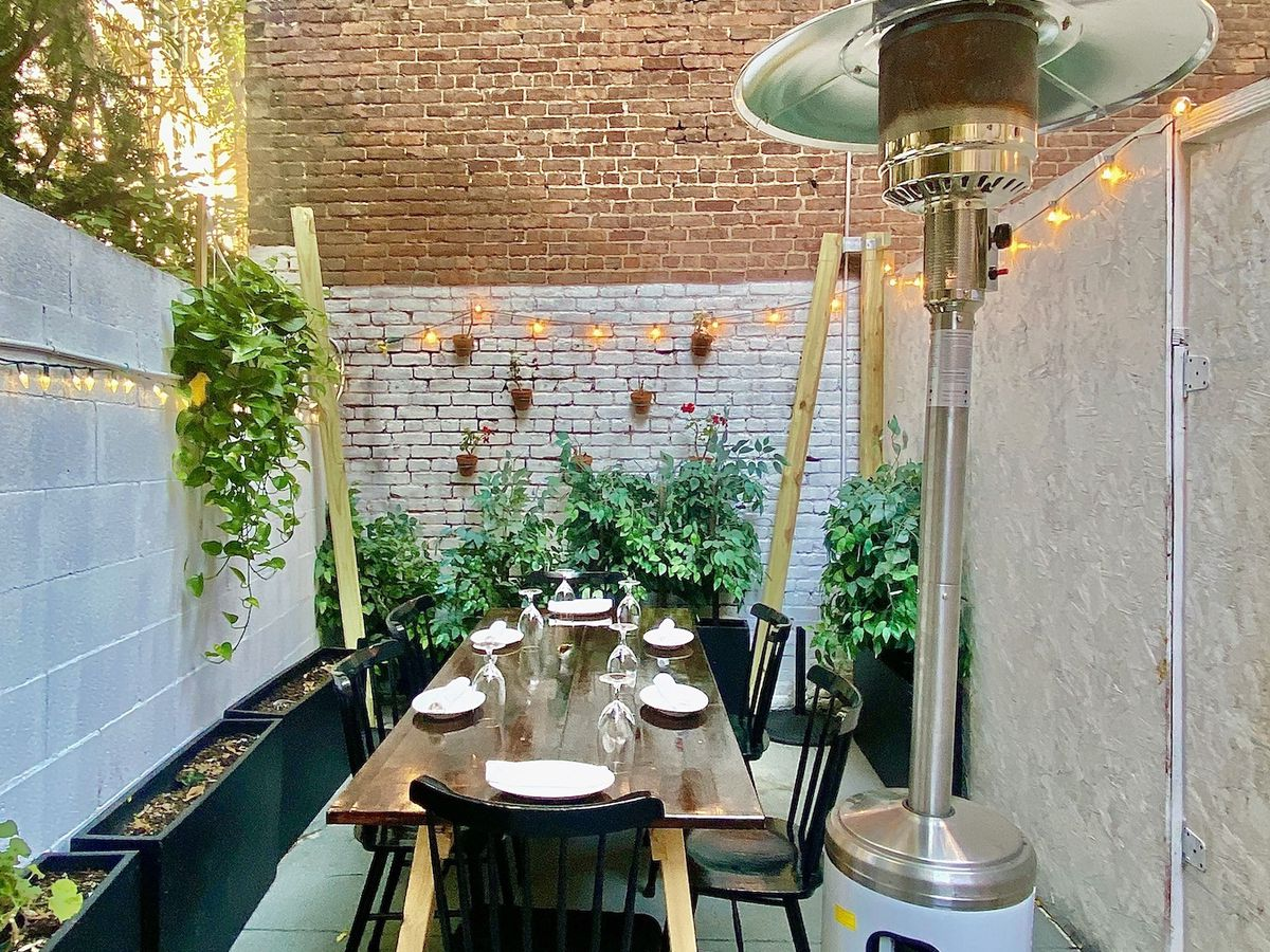 The backyard of the tapas restaurant Socarrat, which has a table and a space heater