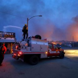 Firefighters spray water on a restaurant to help protect it from flames in the Glenn Ilah area near Yarnell, Ariz. on Sunday, June 30, 2013. An Arizona fire chief says the wildfire that killed 19 members of his crew near the town was moving fast and fueled by hot, dry conditions. The fire started with a lightning strike on Friday and spread to 2,000 acres on Sunday amid triple-digit temperatures. (AP Photo/The Arizona Republic, David Kadlubowski)