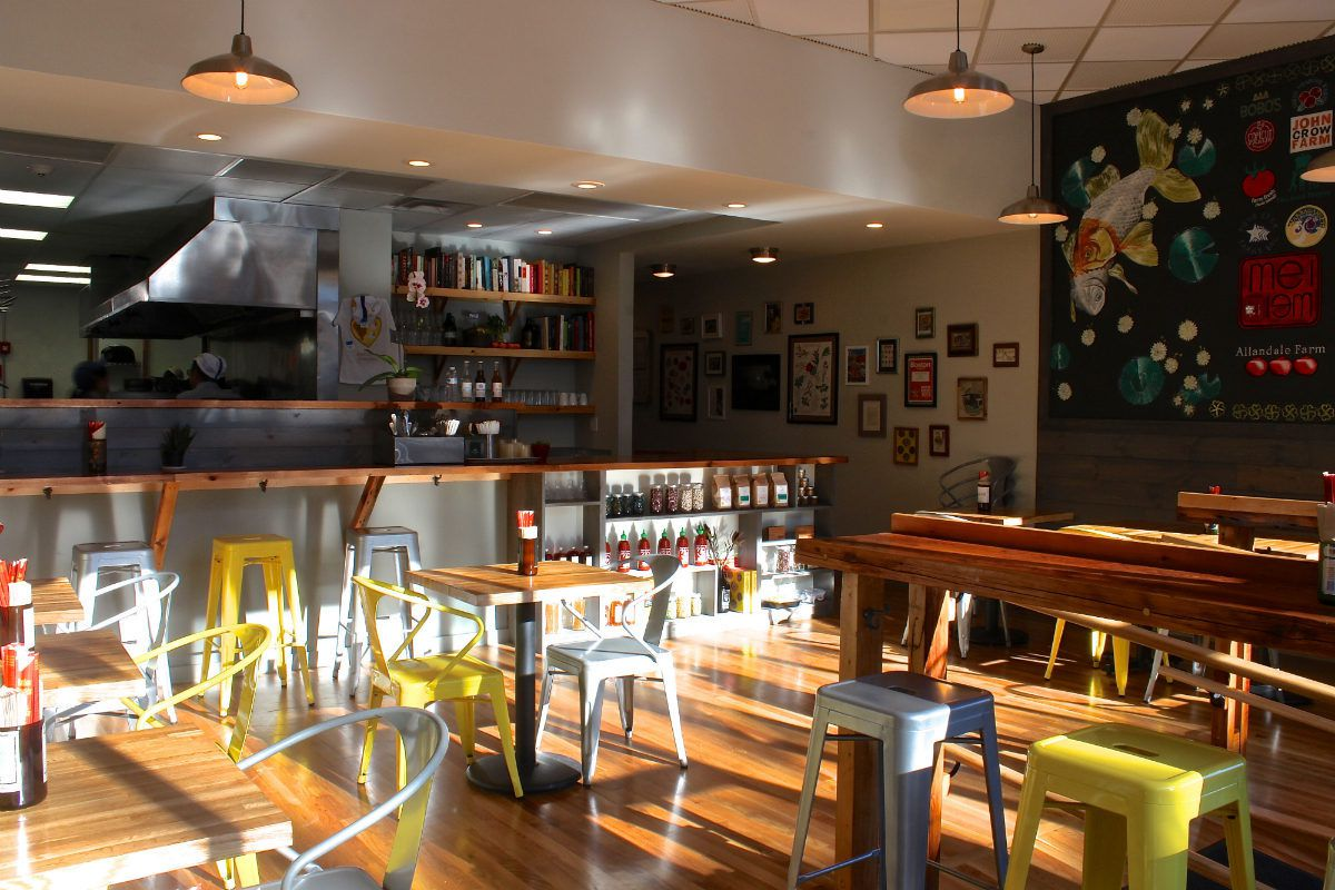 A casual restaurant interior with sunlight streaming in. There are light wooden surfaces, an open kitchen, and yellow and white metal chairs.