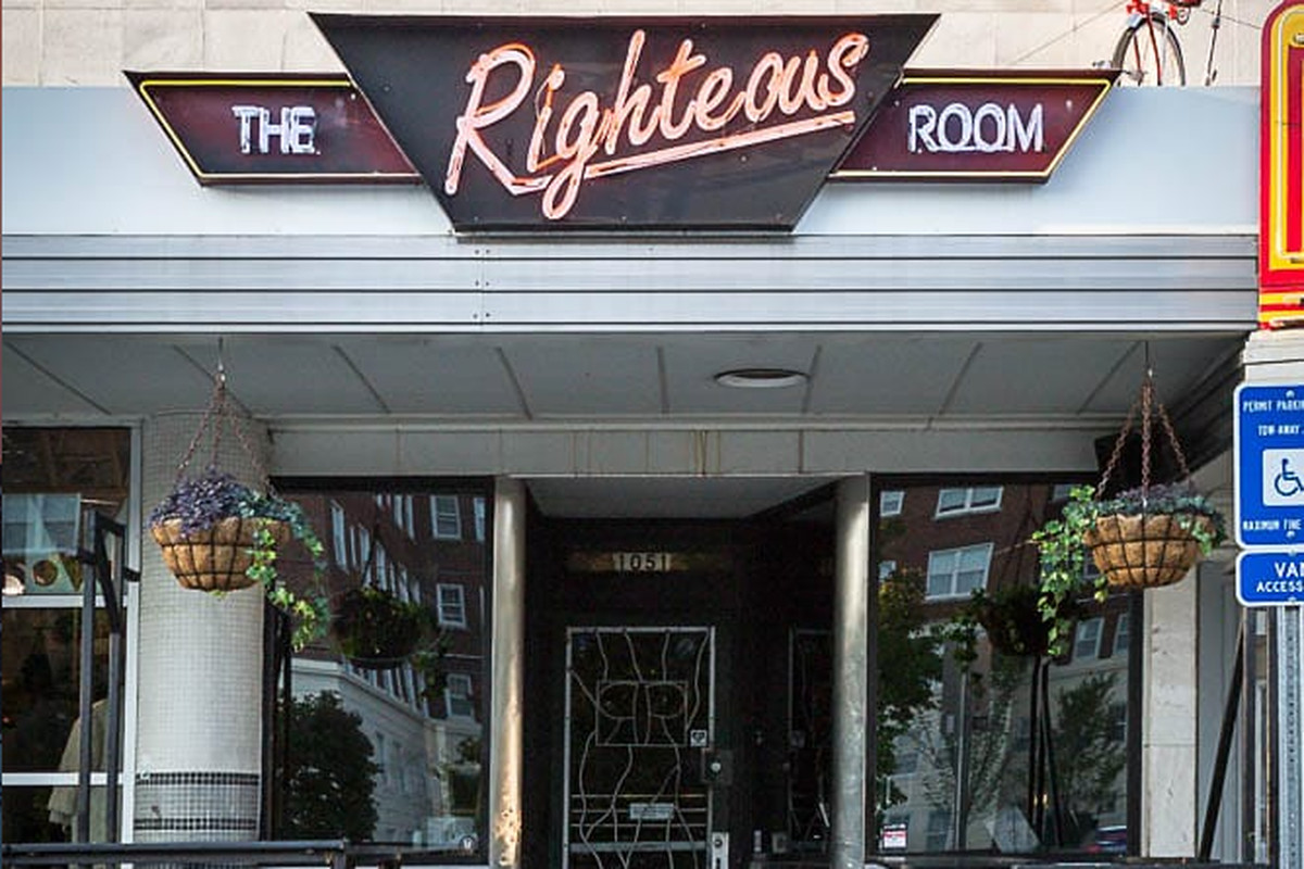 The outdoor seating at the Righteous Room in Poncey-Highland Atlanta with two hanging flower baskets and neon sign lit up