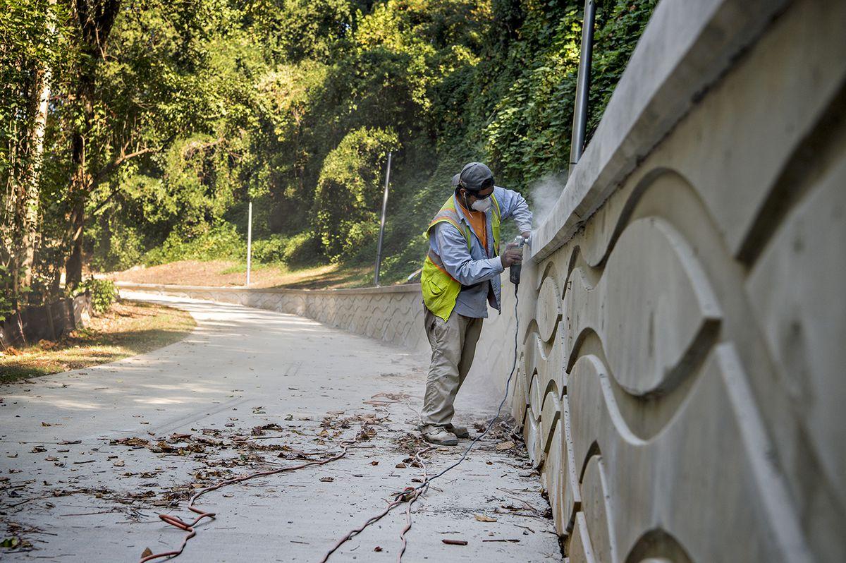 A worker sands down a long wall beside a multiuser trail.