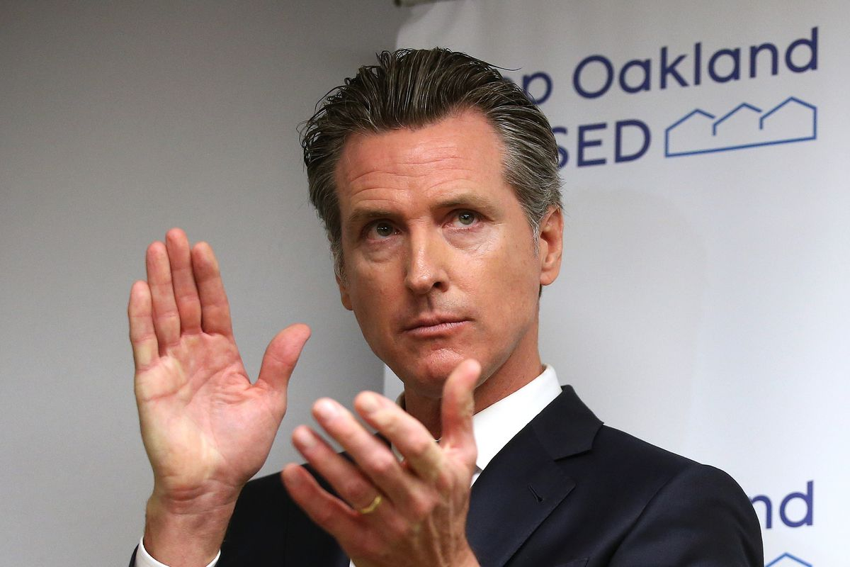 Governor Gavin Newsom in the middle of applauding.