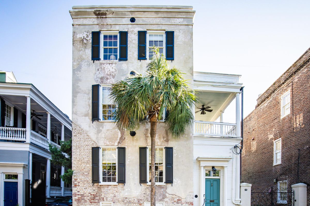 An exterior view of a three-story white historic building with shutters and a single palm tree in front.