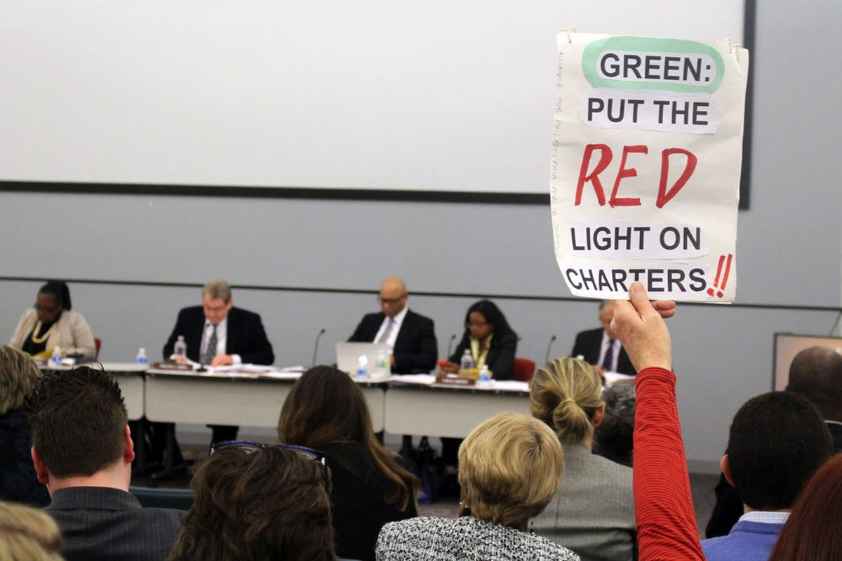 A sign being held up by an audience member at a meeting that reads: Green: put the RED light on charters!