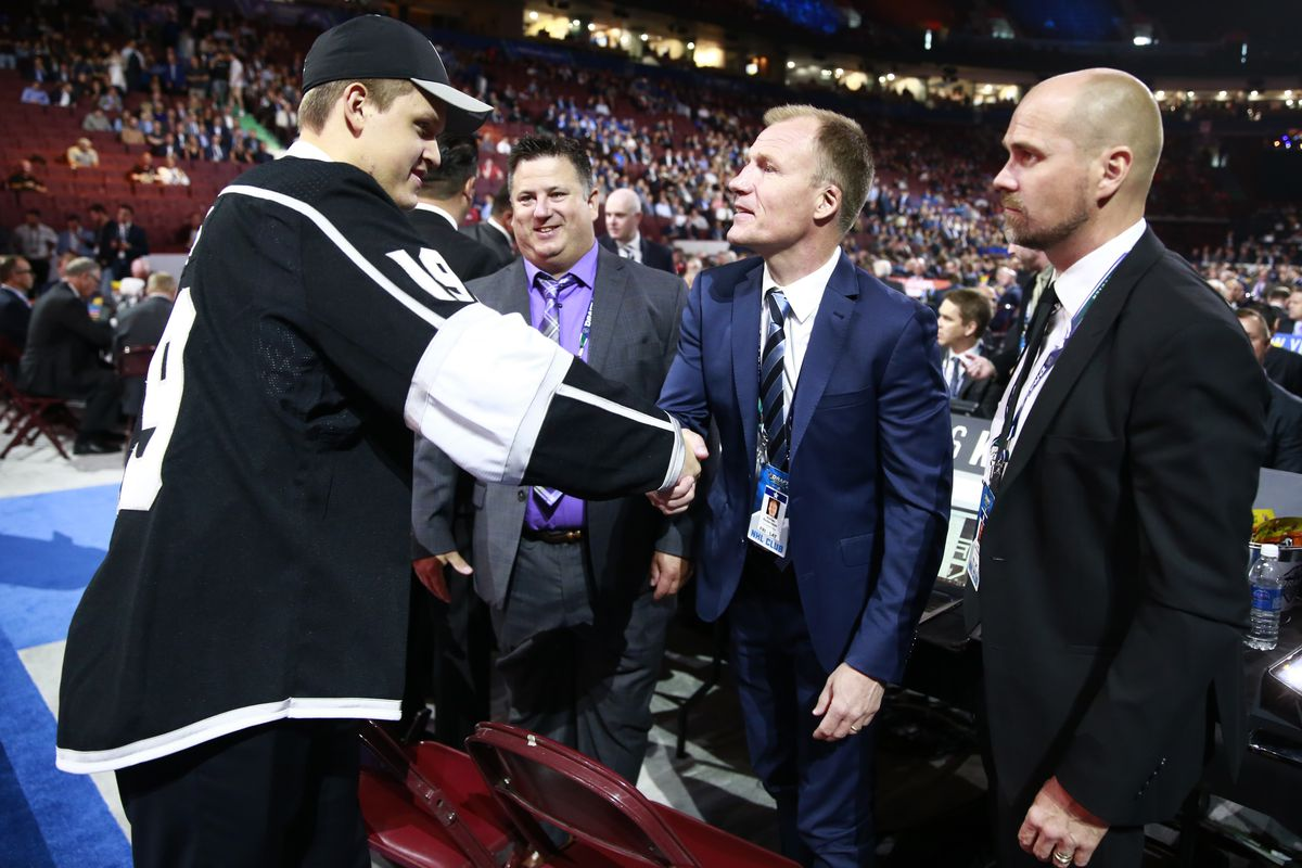 Arthur Kaliyev, 33rd overall pick of the Los Angeles Kings, is greeted by Niklas Andersson of the Los Angeles Kings at the team draft table during Rounds 2-7 of the 2019 NHL Draft at Rogers Arena on June 22, 2019 in Vancouver, Canada.