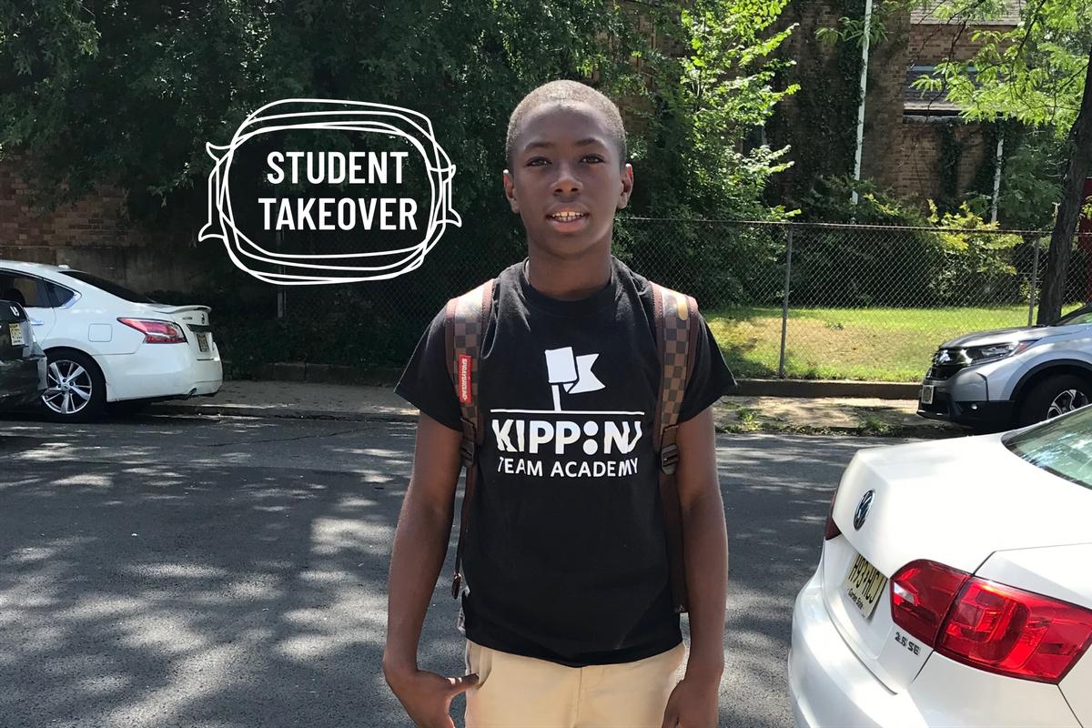Jasin Shiggs, wearing a black KIPP Academy t-shirt and khakis, standing outside smiling.