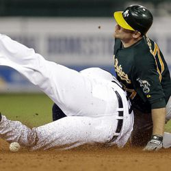 Oakland Athletics' Brandon Moss, right, slides safely into second base for a double as Detroit Tigers first baseman Prince Fielder slides into him trying to catch the ball and make a play in the fifth inning of a baseball game in Detroit on Tuesday, Sept. 18, 2012.