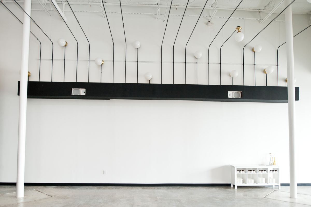 big, empty white room with arty lights starting at the top of wall and extending over room