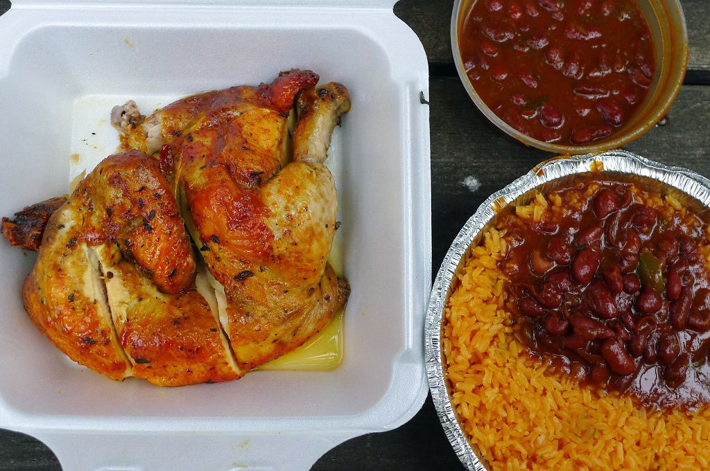 A paprika rubbed half chicken with rice and red bans on the side.
