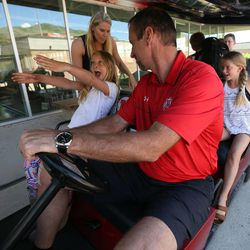 Larry Krystkowiak, head coach for the Utah Runnin' Utes basketball team, gets ready to drive his family to their car in a golf cart with his wife Jan, and daughters Finley, left, and Sam at the University of Utah in Salt Lake City on Friday, June 12, 2015.