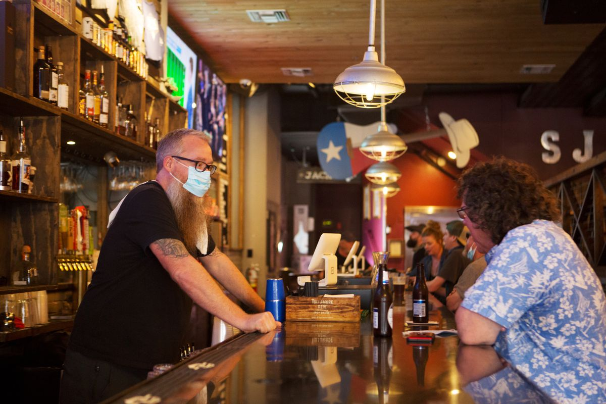 A masked bartender serving a customer at an Austin bar in March