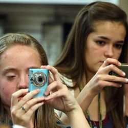 Jessica Crawford and Amanda Sinclair shoot photos of David Archuleta as he signs books and cds during a book signing event at the Deseret Book at Ft. Union in Midvale on Nov. 22.