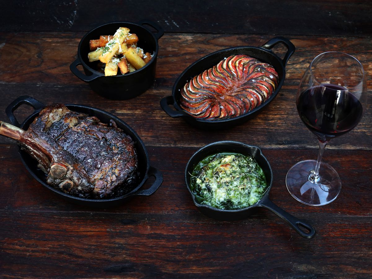 A steak and side dishes in cast iron cookware on a wood table.