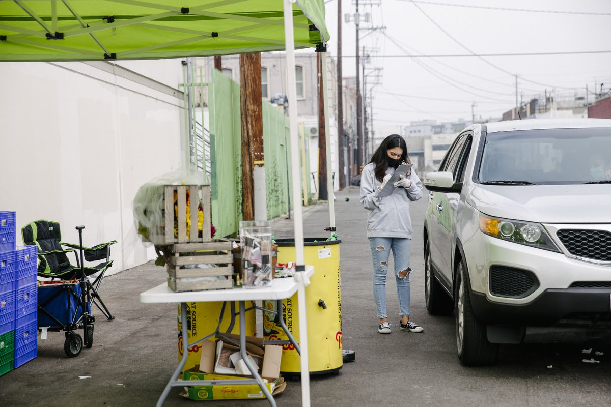 Woman checks a clipboard while standing alongside an SUV that has pulled up to a covered tent.