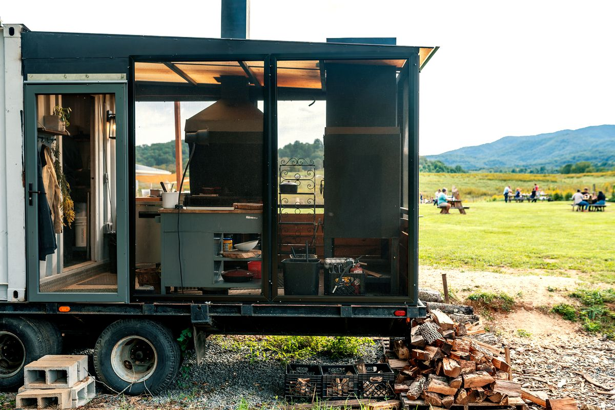 A view of two black, custom wood-burning hearths through the open, framed walls of a trailer extension that looks out over a field with a mountainous backdrop.